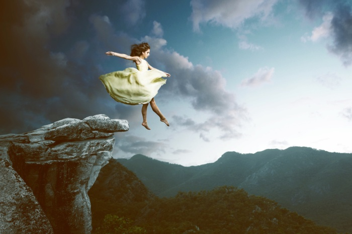 Woman jumps from a high rock
